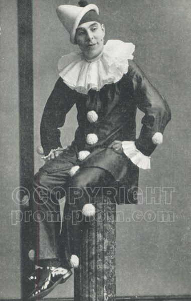 Will Catlin in dark pierrot costume posed on pillar