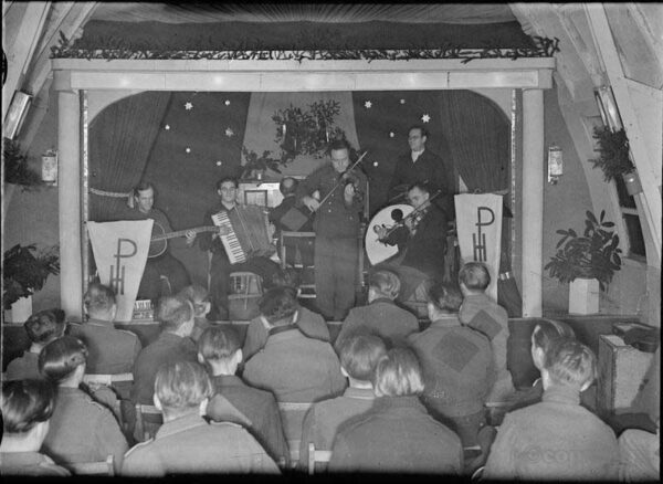 German Prisoners of War listen to a concert given by their fellows, on the stage of the recreation hut at a PoW camp, somewhere in Britain a