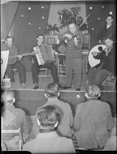 German Prisoners of War listen to a concert put on by fellow prisoners on the stage at a PoW camp, somewhere in Britain
