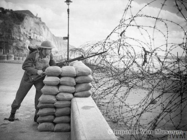 THE BRITISH ARMY IN THE UNITED KINGDOM 1939-1945 (H 4733) Posed portrait of a soldier with rifle and bayonet standing watch behind beach defences 'somewhere in Southern Command', England, 15 October 1940.