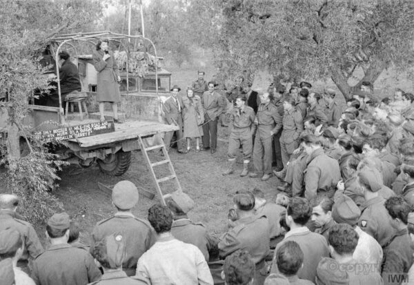 Ruth Howard, entertains personnel of No_244 Wing RAF at Canne, Italy, during a visit by Geraldo and his band