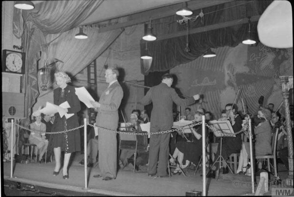 Tommy Handley (centre) introduces new singer Ann Rich to the 'It's That Man Again' audience, as Charlie Shadwell conducts the BBC Variety Orchestra behind them